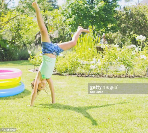 Girl doing cartwheels in backyard