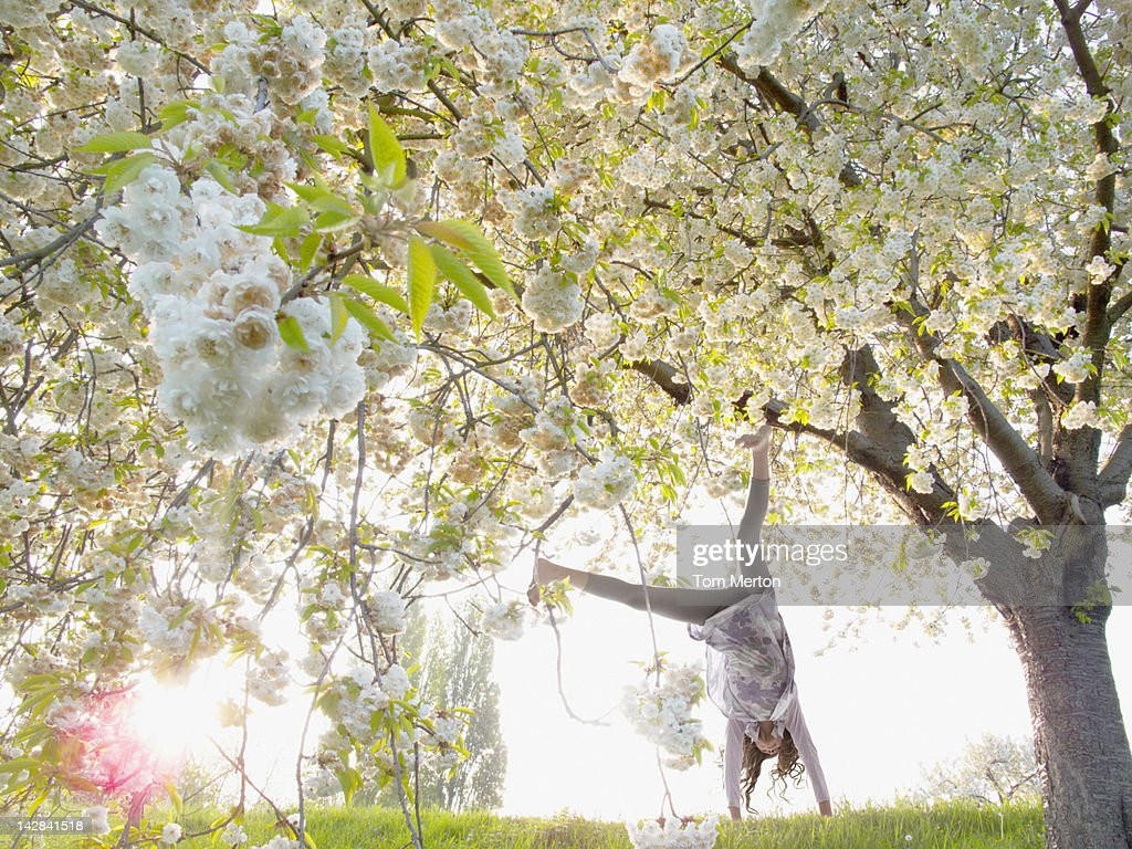 Girl doing cartwheels under flowering tree