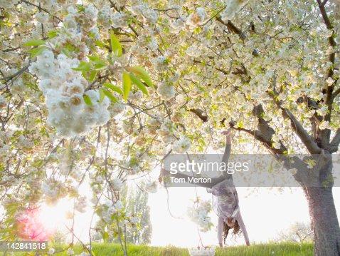 Girl doing cartwheels under flowering tree : Stock Photo