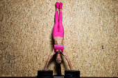 Fitness instructor performing handstand on the wall