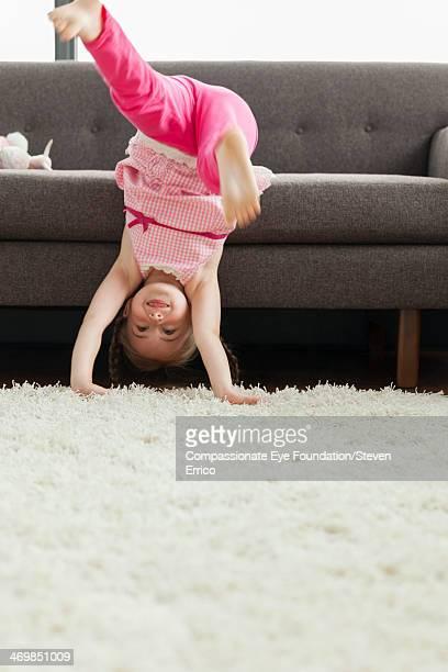Girl (6-7) doing handstand in living room