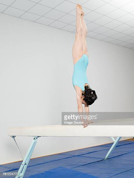 Girl doing handstand on balance beam