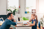 Girl doing homework and contemplating with father