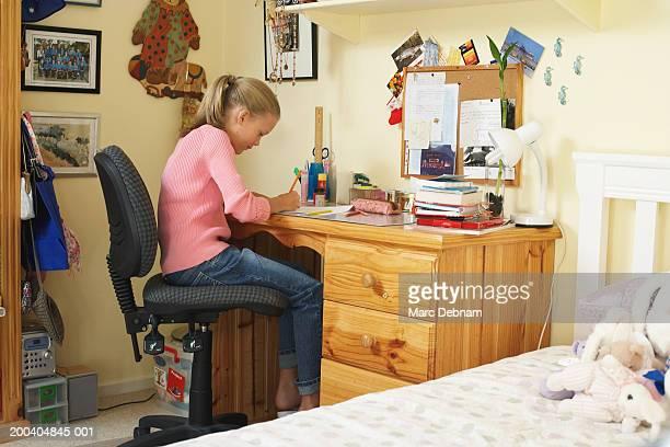 Girl (10-12) doing homework at desk in bedroom, side view