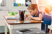 Little Girl in blue shirt doing homework on old wooden desk and using ruler