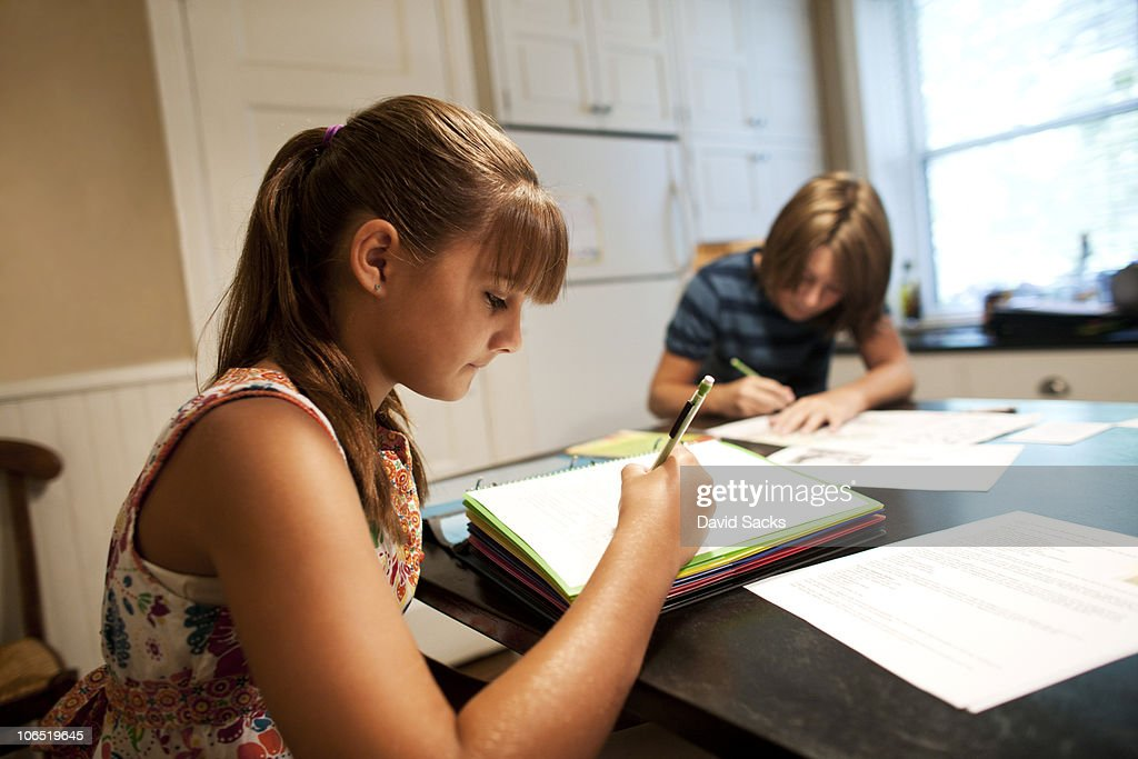 Girl doing homework with brother in background