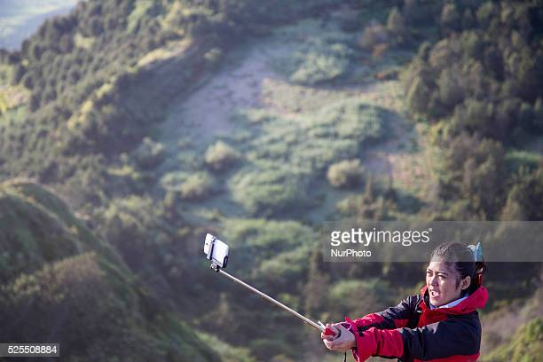 A girl doing selfie at the top of Sikunir Mountain in Dieng Dieng plateau in Central Java is part of the district of Banjarnegara and Wonosobo...