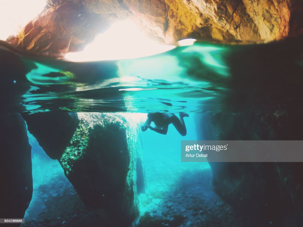 Girl doing snorkel exploring the natural cave in the shoreline of Costa Brava Mediterranean Sea during summer vacations in a paradise place taking picture with dome cover and underwater view. : Stock Photo