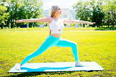 Girl doing yoga on grass in a park