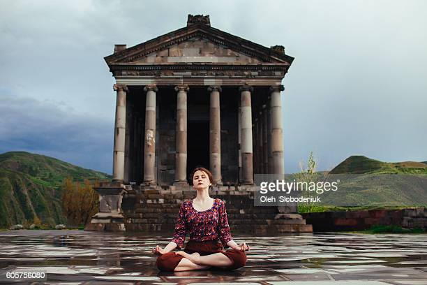 Girl doing yoga near the ancient temple