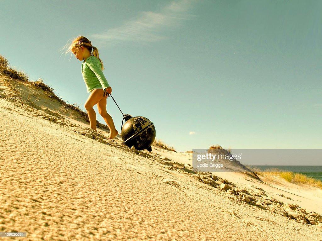 Girl dragging buoy up sand dune : Stock Photo
