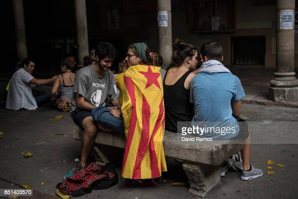 A girl draped in a Catalan proindependence flag 'Estelada' sits on a bench inside the rectory of the University of Barcelona during a protest on...