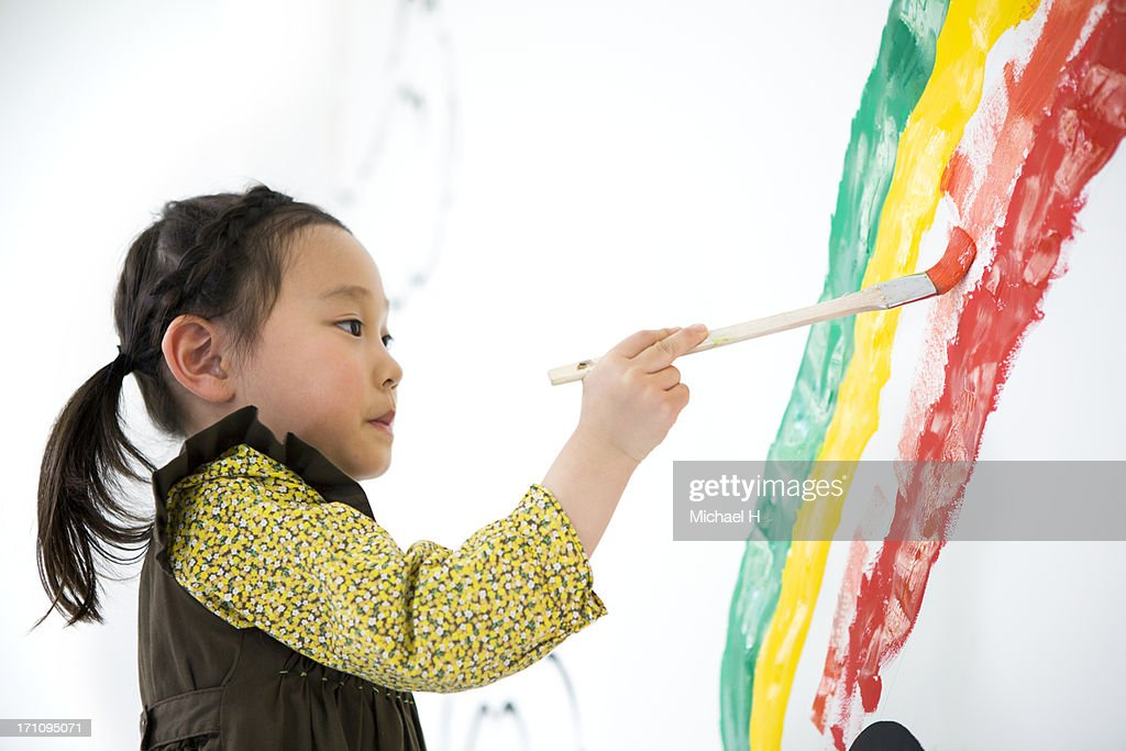 Girl draw rainbow on the wall : Stock Photo