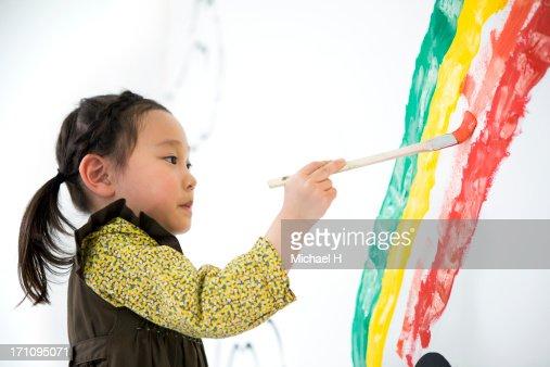 Girl draw rainbow on the wall : Stock Photo