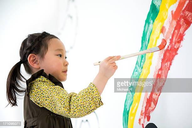 Girl draw rainbow on the wall