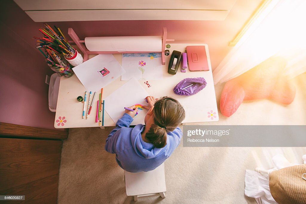 Girl drawing at desk : Stock Photo