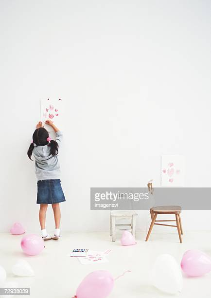 Girl drawing by wall