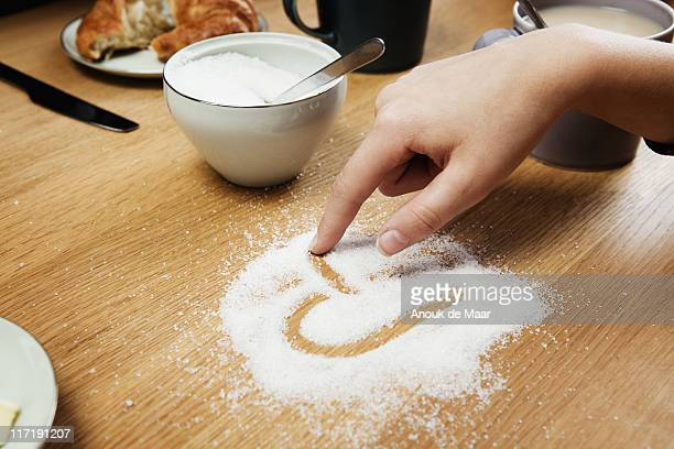 Girl drawing hart in sugar on table