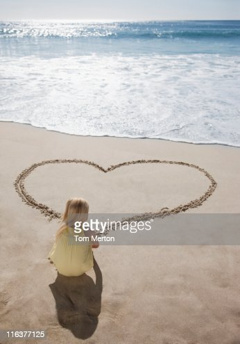 Girl drawing heart in sand on beach : Stock Photo