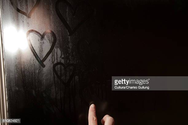 Girl drawing heart shape in condensation on window