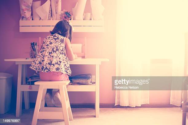 Girl drawing her in bedroom