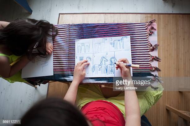Girl drawing her plan for a horse to be crafted