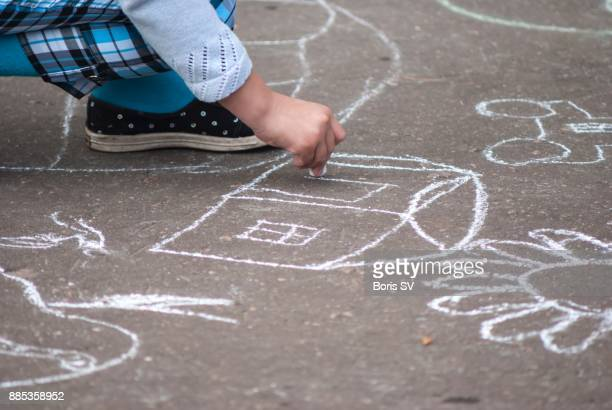 Girl drawing house on asphalt with chalk