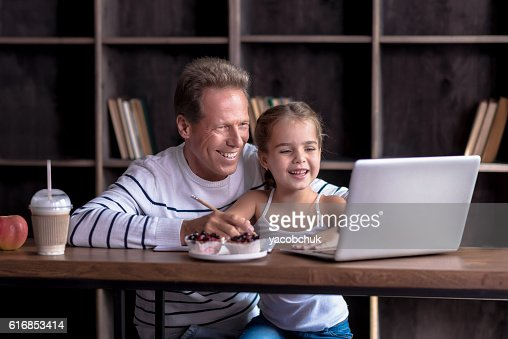 Girl drawing in front of the computer with her grandfather : Stock Photo