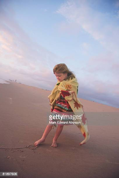 Girl drawing in sand with toe