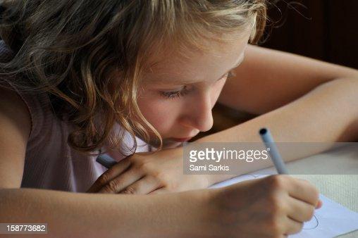 Girl (8) drawing, indoors : Stock Photo