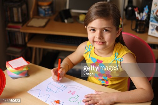 Girl drawing on a paper : Stock Photo