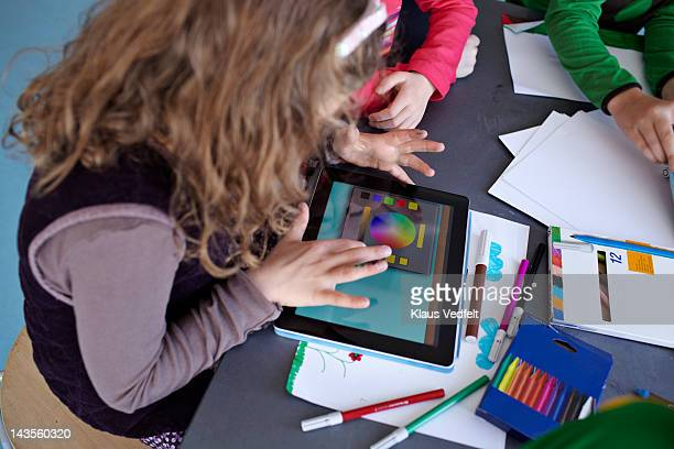 Girl drawing on tablet with classmates