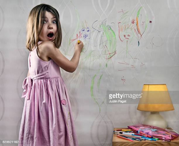 Girl (7-9) drawing on wall