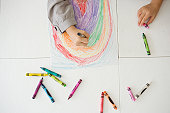 Girl drawing rainbow with crayon,