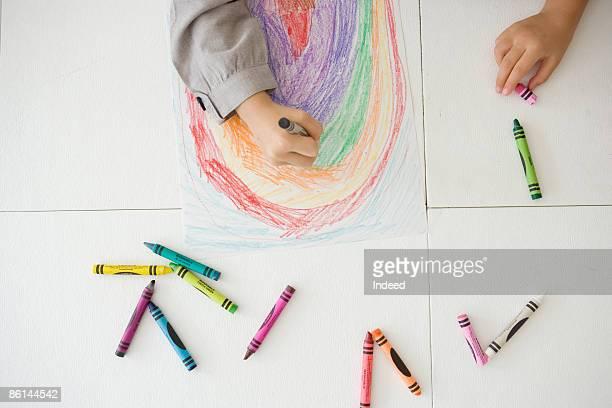 Girl drawing rainbow with crayon,