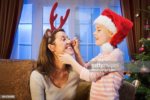 Girl drawing red reindeer nose on mother's face
