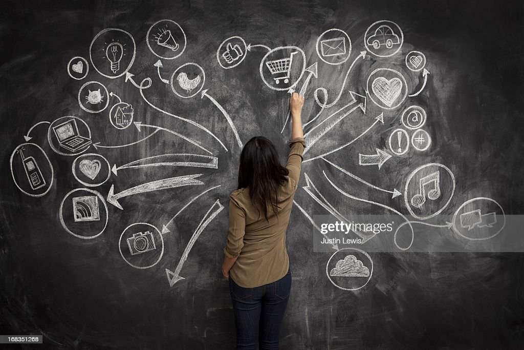 Girl drawing social meida icons on chalkboard : Stock Photo