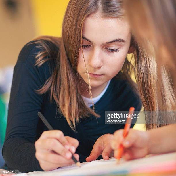 Girl drawing with color pencils in the class room