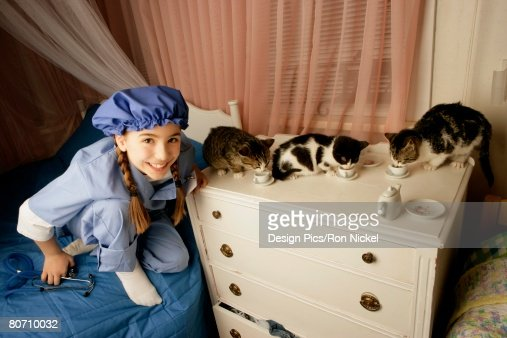 Girl dressed as a veterinarian with three cats : Stock Photo