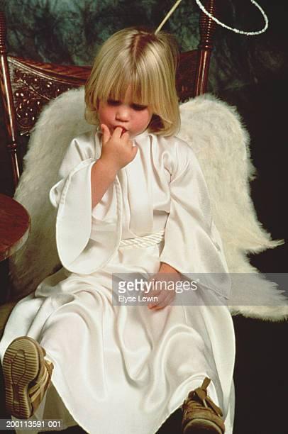 Girl (4-6) dressed as angel sucking finger