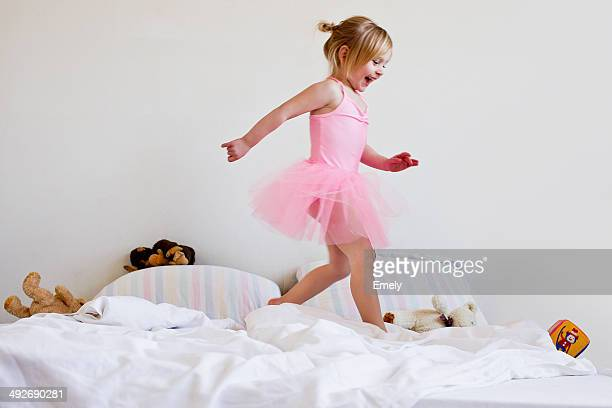Girl dressed as ballet dancer running on bed