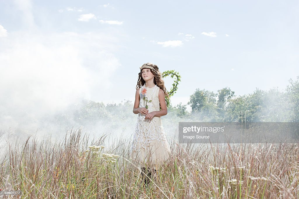 Girl dressed as fairy in field with flower