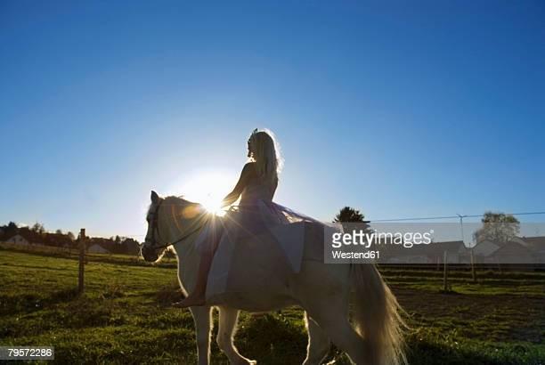 'Girl dressed as princess, riding horse'