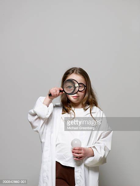 Girl (8-10) dressed as scientist using magnifying glass