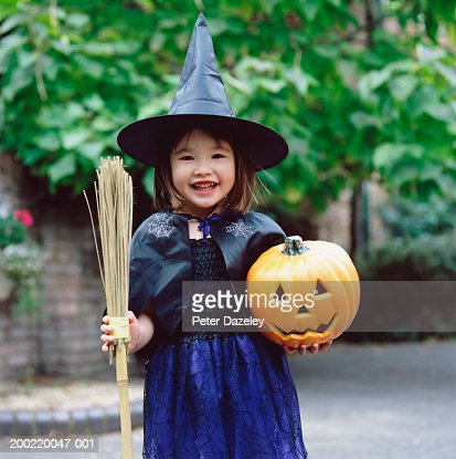Girl (3-5) dressed as witch, holding pumpkin and broom, portrait : Stock Photo
