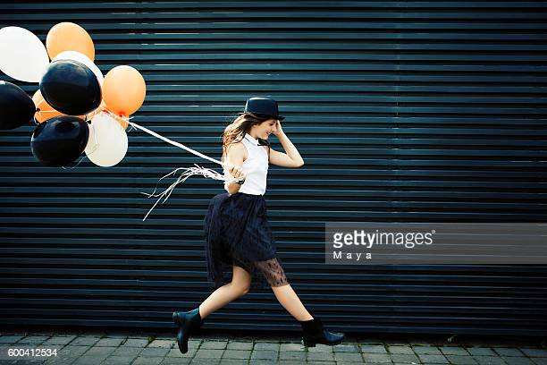 Girl dressed for Halloween jumping with balloon