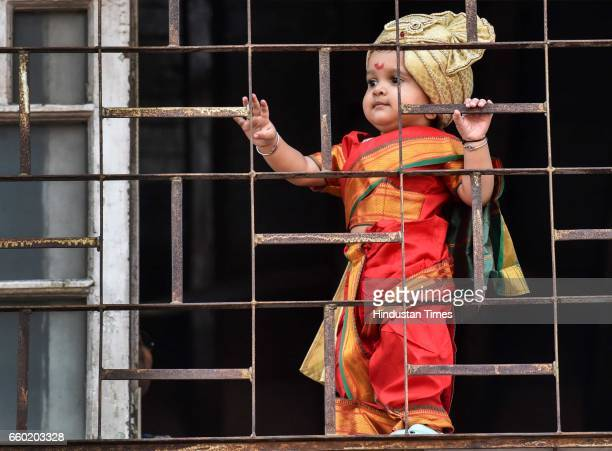 A girl dressed in traditional attire watch the procession celebrating 'Gudhi Padwa' or the Maharashtrian New Year from her balcony at Girgaum on...