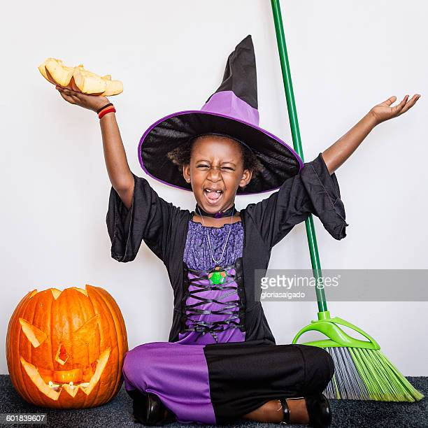 Girl dressed in witch costume with pumpkin at Halloween