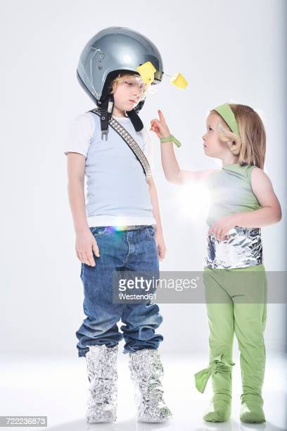 Girl dressed up as alien getting in contact with boy dressed up as spaceman