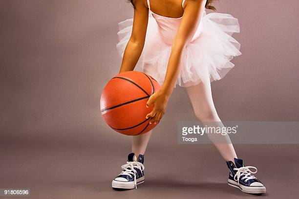 Girl dribbling basketball wearing ballet outfit
